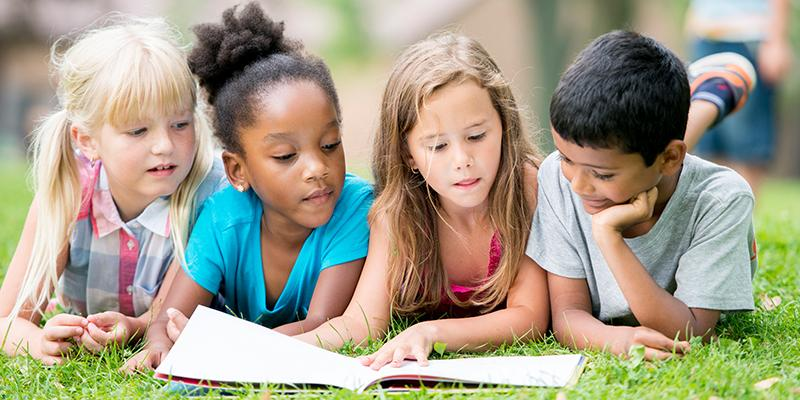 Four children reading in the grass
