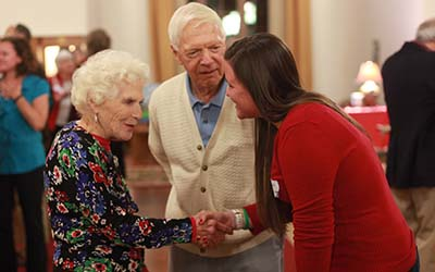 Bryn Athyn College students shakes hand of elderly lady