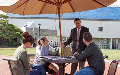 Bryn Athyn College professor speaking with students at an outdoor patio table