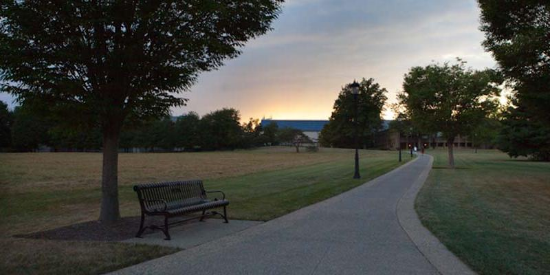 Bryn Athyn Collge view of the campus meadow and the sun setting behind the library