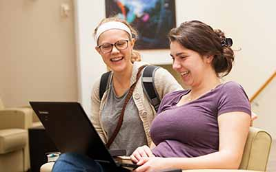 Bryn Athyn College students looking at laptop smiling